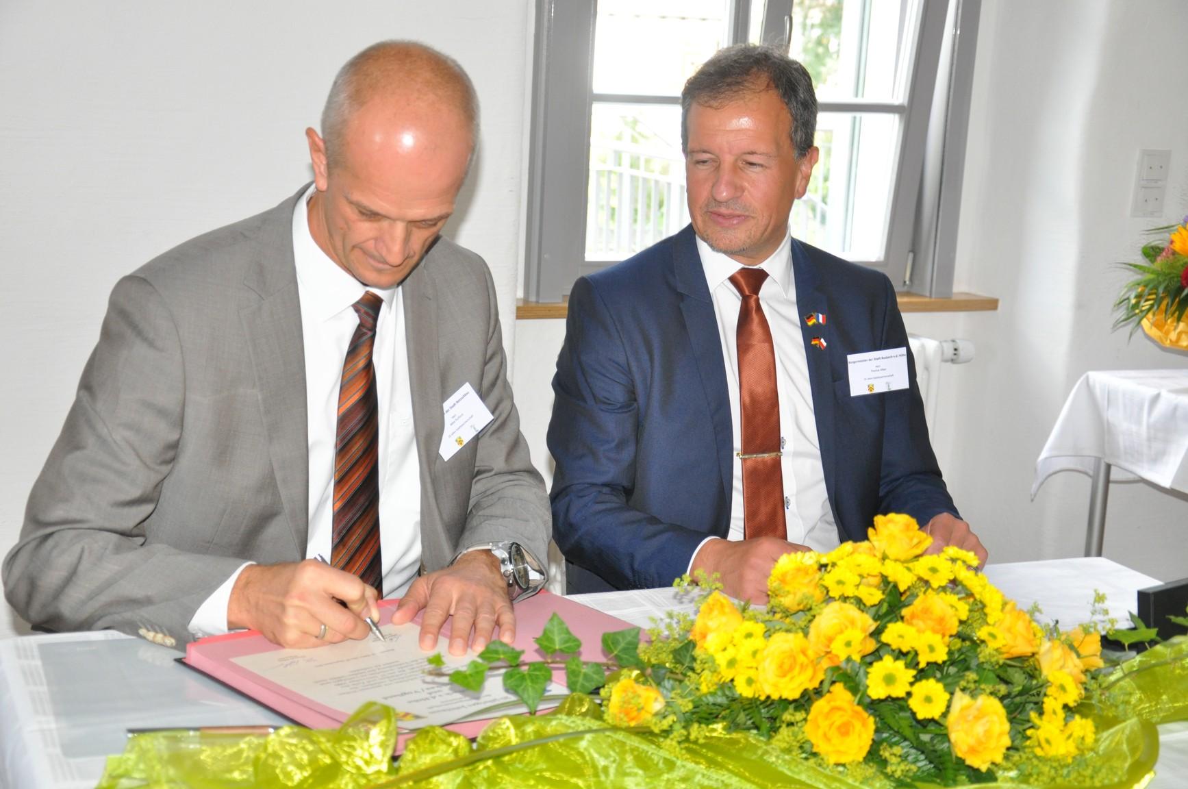 Bürgermeister Thomas Alber (rechts) und Mike Purfürst (links) beim unterzeichnen der Urkunde.